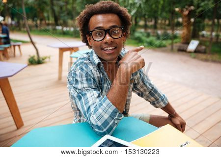 Cheerful african young man in glasses siting in cafe and pointing away