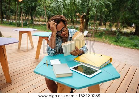 Pensive african young man reading and studying in outdoor cafe