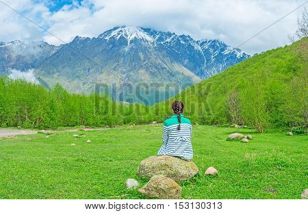 The best way to relax during the long mountain climb is to sit on some scenic forest glade Kazbegi National Park Georgia.