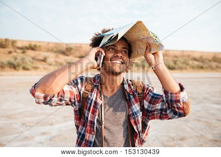 Happy african american young man covered head with map and talking on cell phone