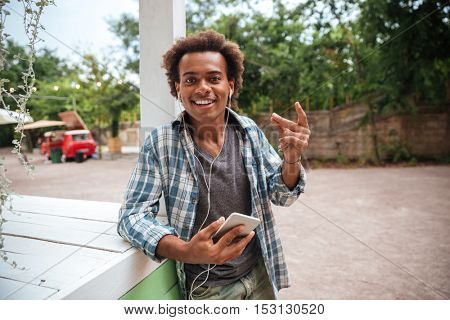 Happy african young man listening to music from cell phone and having fun