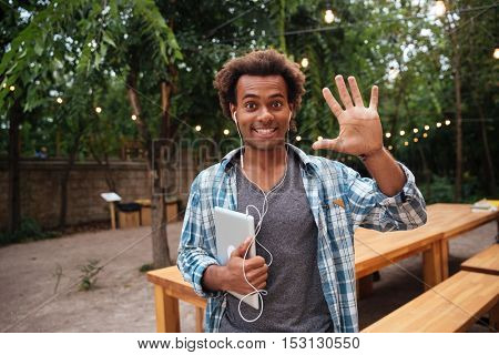Cheerful african young man with tablet standing outdoors and saying hello
