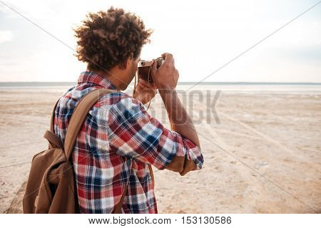 Back view of african american young man with backpack taking photos on the beach