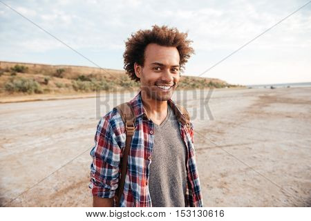Smiling handsome african young man with backpack standing on the beach