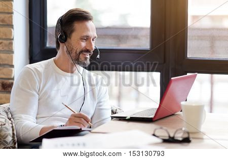 Working for result. Smiling bearded man wearing headphones taking notes looking while looking at modern laptop against big window.