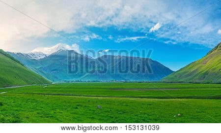The juicy greenery of the meadows in Sno valley with the uncovered peak of Kazbek Mount on background Kazbegi Georgia.