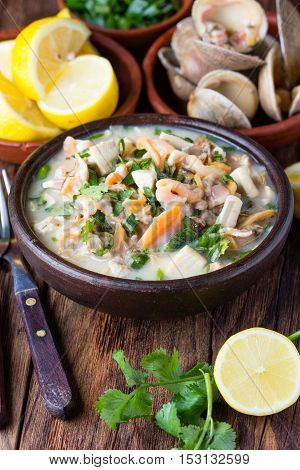 Latin American food. Seafood shellfish ceviche - raw cold soup mariscal or salad of seafood shellfish, lemon, cilantro onion in clay bowl on wooden background. Traditional dish of Peru or Chile
