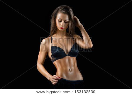 Portrait of the perfect fitness woman in black lingerie on the black background. Beauty fitness portrait.