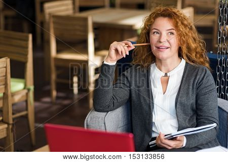Getting idea. Thoughtful ginger-haired woman holding pencil at her cheek and some notes while sitting in cafe.