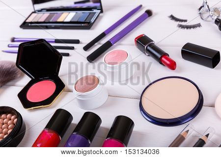 closeup of makeup cosmetics on wooden table