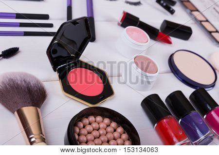 collection of makeup cosmetics products on wooden table