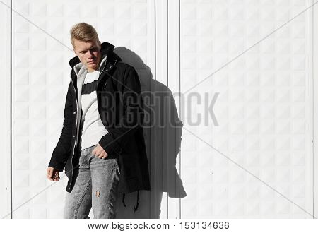 Young blonde man in autumn clothes standing near white wall.
