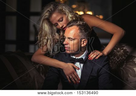 Seductive woman touching man in tuxedo with both hands