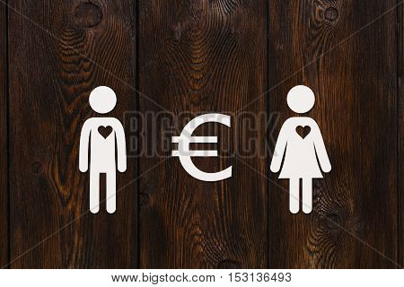 Paper man, woman and euro sign on dark wooden background. Love relation and money concept. Abstract conceptual image