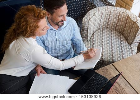 Necessary information. Top view of smiling ginger woman making notes in notebook of bearded man holding it.