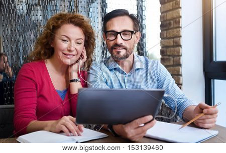 Watching video tutorials. Man holding tablet and taking notes while he together with his female partner getting information through earphones.