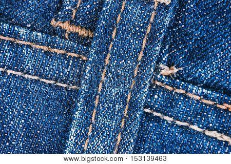 Macro flat view of blue denim jeans details with decorative stitch