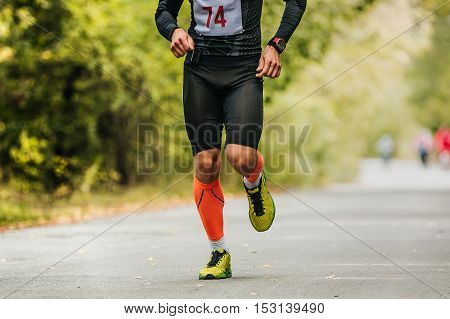 sports young male athlete running in autumn forest marathon