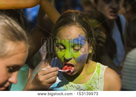 Lviv Ukraine - August 28 2016: Girl eats watermelon plastic spoon during the festival of color in a city park in Lviv.