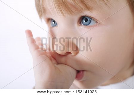 photo of little beautiful girl holding finger in mouth
