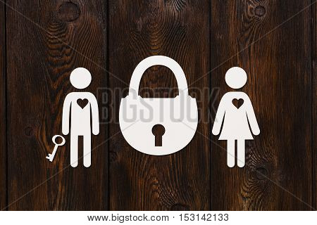 Paper man with key, woman and padlock on dark wooden background. Love relation concept. Abstract conceptual image