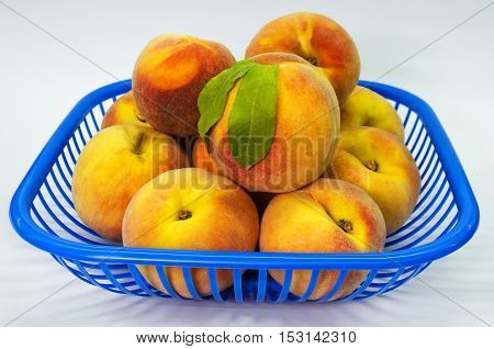 a basket of fresh peaches on a white background