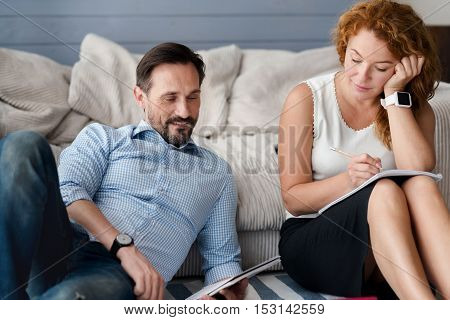 Concentrated on purpose. Nice couple holding notebooks and learning while sitting on floor in front of couch