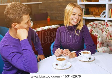 Young man drinking coffee and talking with a woman