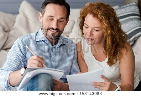 Developing new ideas. Nice middle-aged couple holding notebooks and looking at them while sitting on couch.