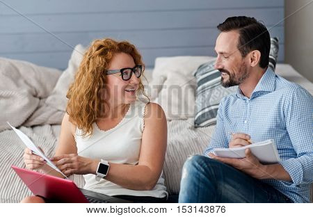 Ins and outs. Pretty smiling ginger woman using laptop holding some notes and looking at bearded man with notebook.