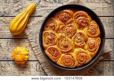 Pumpkin cinnamon bun rolls homemade baked sweet autumn dessert bread food on vintage wooden table background