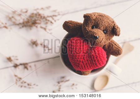 Teddy bear with red heart shape in cup of coffee on white wooden background Vintage tone