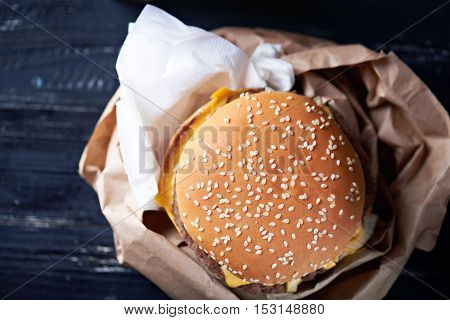 Unhealthy cheeseburger in the paper container with paper napkins on a dark wooden background. Close up