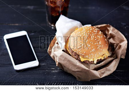 Cheeseburger in the paper container with paper napkins on a dark wooden background with moblie phone