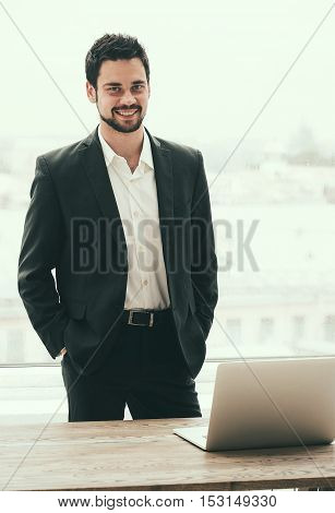 Happy Young Man Working On Laptop While Sitting At His Working Place In Office