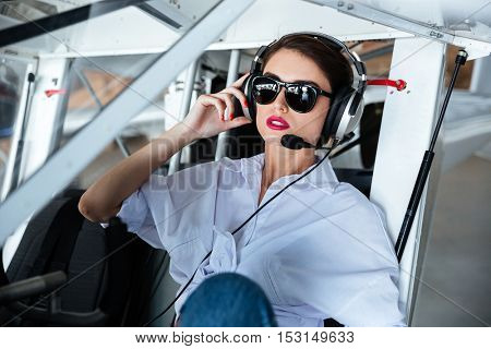 Portrait of attractive young woman pilot in sunglasses and headset sitting in small aircraft