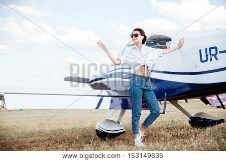 Full length of smiling gorgeous young woman standing near small plane