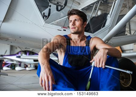 Young handsome mechanic in overall holding wrench resting at the shed