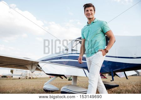 Cheerful young man walking in field near private aircraft