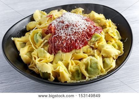 Traditional Italian homemade spinach and ricotta tortellini With marinara souce and parmesan.