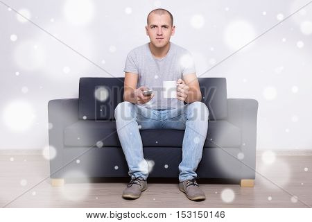 Young Man Sitting On Sofa With Cup Of Tea And Watching Tv At Home