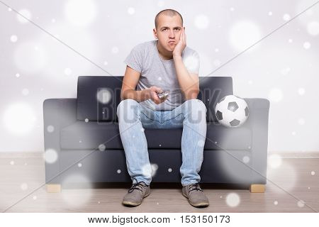 Bored Soccer Fan With Ball Watching Game On Tv