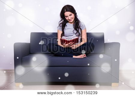 Winter Leisure Concept - Woman Sitting On Sofa And Reading Book