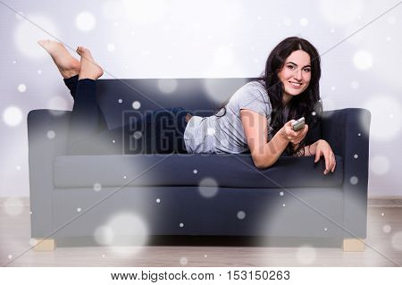 Winter Leisure Concept - Woman Lying On Sofa And Watching Tv At Home