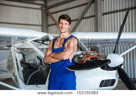 Happy attractive young aircraft mechanic standing with arms crossed near small airplane