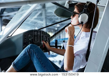 Attractive young woman pilot sitting and talking with headset in small plane