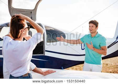 Cheerful young pilot inviting passengers on board of private airplane