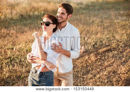 Happy couple in love standing at the field during sunset and hugging