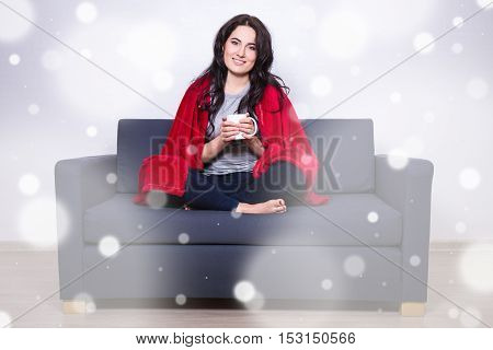 Winter Concept - Young Woman Sitting On Sofa With Mug Of Tea Wrapped In Red Blanket