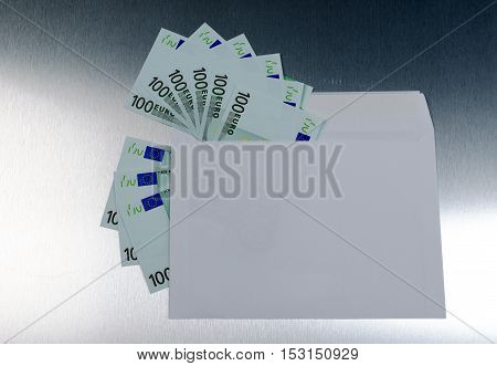 Euro banknotes in envelope over a metall background